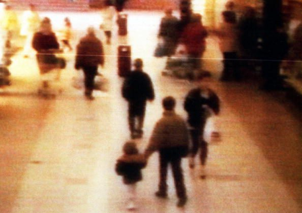 A surveillance camera shows the abduction of two-year-old James Bulger from the Bootle Strand shopping mall Feb. 12 1993 at 3:42pm near Liverpool, England. Bulger holds the hand of Jon Venables, one of two 10-year-old boys later convicted of his torture and murder. (BWP Media via Getty Images)