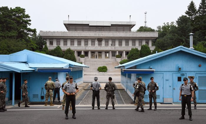 South Korea and U.S. soldiers stand guard during a commemorative ceremony for the 64th anniversary of the signing of the Korean War Armistice Agreement at the truce village of Panmunjom in the Demilitarized Zone (DMZ) dividing the two Koreas on July 27, 2017. On Jan. 9, 2018, high-level representatives from North and South Korea will sit down for a joint meeting in the village to discuss North Korea's participation in the upcoming Olympic Games. (JUNG YEON-JE/AFP/Getty Images)