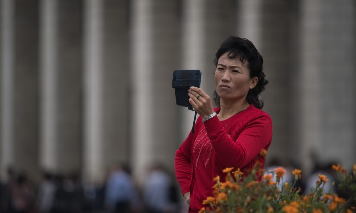A woman uses a mobile phone to record footage as a propaganda troupe perform a flag-waving routine outside the central railway station in Pyongyang on Sept. 27, 2017. (ED JONES/AFP/Getty Images)