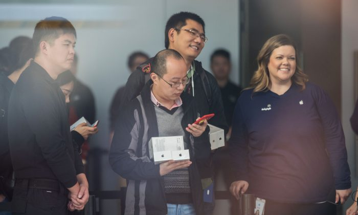 Chinese customers line up at the Apple store while a foreigner Apple staffer stands nearby, in Hangzhou City, Zhejiang Province on November 3, 2017. (STR/AFP/Getty Images)