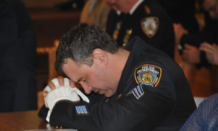 An NYPD Sergeant at prayer in Our Lady of Mount Carmel Church, Brooklyn, NYC, June 26, 2017. A memorial mass was held honoring NYPD Transit Bureau officers who died in the line of duty. The names of 36 fallen officers were read during the mass as attendees prayed for their families. All of the most recent officers being recognized died due to illnesses contracted while working at Ground Zero. (Courtesy NYPD news)