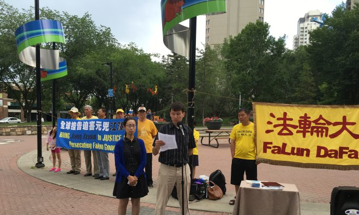 File photo of Jay Brauneisen, whose mother-in-law, Huixia Chen, has been detained in China for her practice of Falun Dafa, speaking at a rally calling for her release on June 30, 2016 in Edmonton, while his wife Hongyan Lu, Chen's daughter, looks on. (Omid Ghoreishi/The Epoch Times)