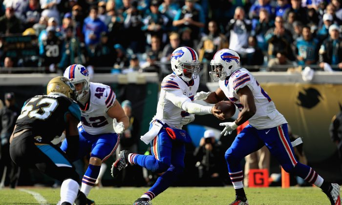 Quarterback Tyrod Taylor #5 of the Buffalo Bills hands the ball off to running back LeSean McCoy #25 in the third quarter against the Jacksonville Jaguars during the AFC Wild Card Playoff game at EverBank Field in Jacksonville, Florida, on Jan. 7, 2018.  (Photo by Mike Ehrmann/Getty Images)