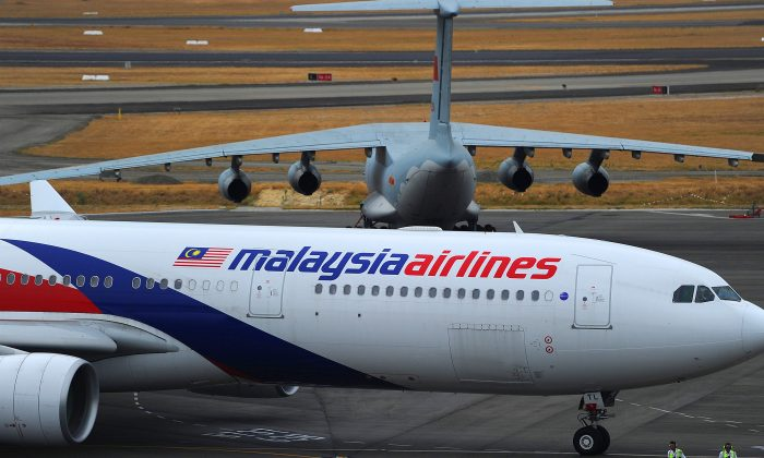 A Malaysia Airlines plane (below) prepares to go onto the runway and pass by a stationary Chinese Ilyushin 76 aircraft (top) at Perth International Airport on March 25, 2014. (Greg Wood/AFP/Getty Images)