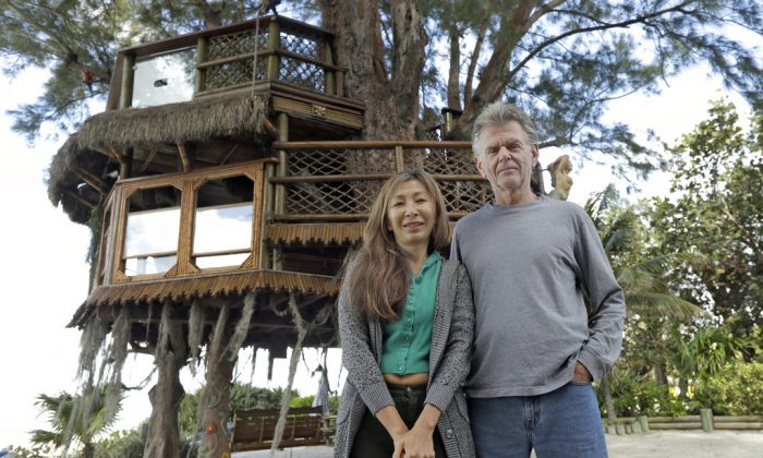 Lynn Tran and her husband Richard Hazen pose near their Australian pine treehouse Thursday, Jan. 4, 2018, in Holmes Beach, Fla. The couple is hoping the U.S. Supreme Court will hear their case after city and state officials ordered the treehouse removed. (AP Photo/Chris O'Meara)