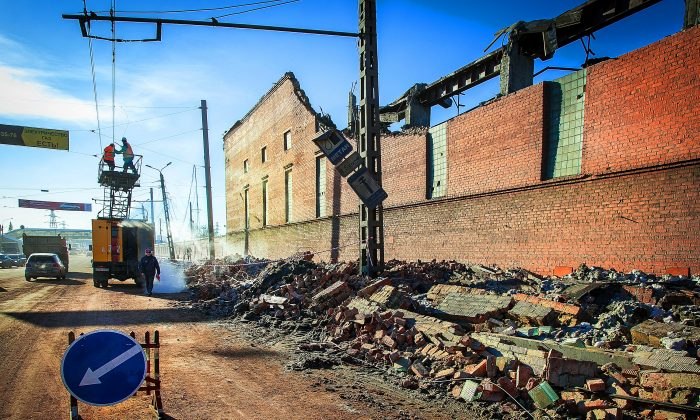 Workers repair a power line near the wall of a local zinc plant which was damaged by a shockwave from a meteor in the Urals city of Chelyabinsk, on Feb. 15, 2013. (Oleg Kargopolov/AFP/Getty Images)