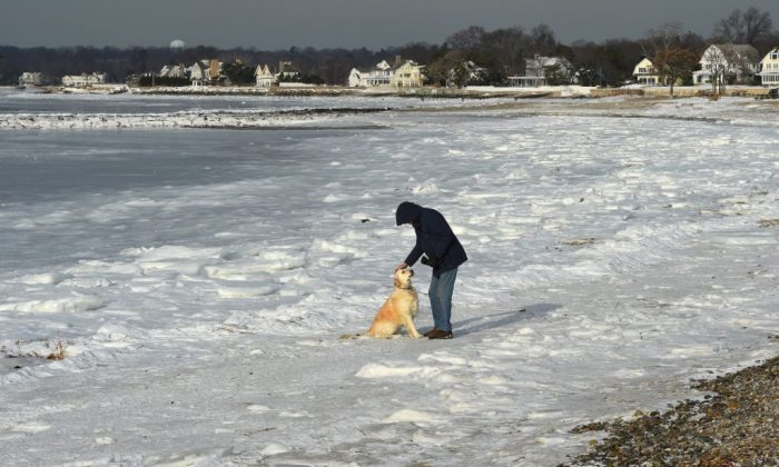 Dick Healy of Wesport, Conn., walks his dog along the frozen Long Island Sound at Compo Beach in Westport, Conn January 8, 2018. The northeast is still facing record low temperatures but warmer weather is on the way. (Timothy A. Clary/AFP/Getty Images)
