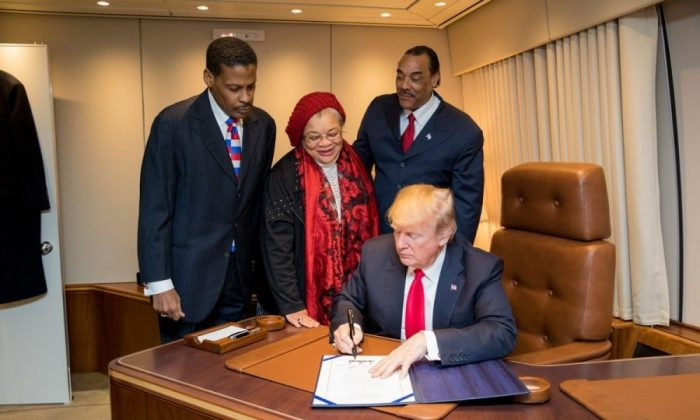 President Donald J. Trump, with Alveda King (C) niece of slain Civil Rights leader Dr. Martin Luther King Jr., and Isaac Newton Farris Jr. (L), nephew of Dr. King, and Bruce Levell of the National Diversity Coalition for Trump (R), signs the Martin Luther King, Jr. National Historical Park Act aboard Air Force One in Atlanta on Jan. 8, 2018. (Official White House Photo by Shealah Craighead)