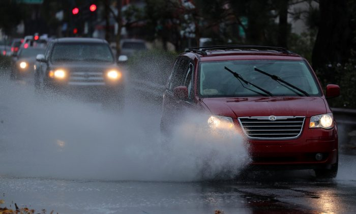 Drivers make their way along a rain soaked road as Souther California is effected by the first winter rainstorm of the season in Encinitas, California, U.S., January 9, 2018.      REUTERS/Mike Blake