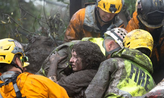 Emergency personnel carry a woman rescued from a collapsed house after a mudslide in Montecito, California, U.S. Jan. 9, 2018. (Kenneth Song/Santa Barbara News-Press via Reuters)