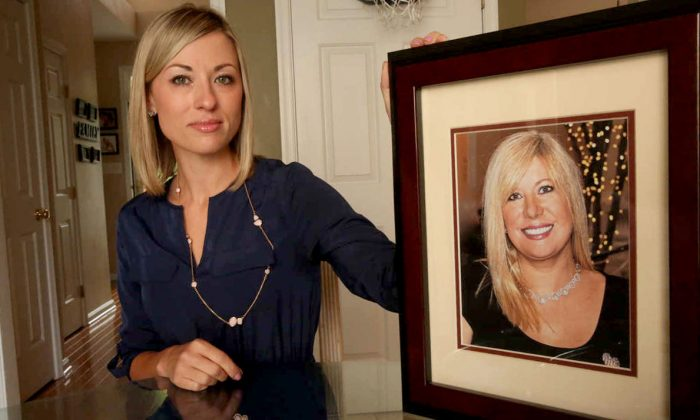 In this May 25, 2016, photo, Kim Pack poses with a photo of her late mother, talk-show host April Kauffman, in Linwood, N.J. Pack's stepfather, Dr. James Kauffman, was charged in the murder of her mother April on Tuesday, Jan. 9, 2018. Kauffman, a New Jersey doctor running an illegal prescription opioid drug ring with a motorcycle gang had a member hire someone to kill his wife after she threatened to expose the scheme while trying to force him to agree to a divorce, authorities said Tuesday. (Vernon Ogrodnek/The Press of Atlantic City via AP)