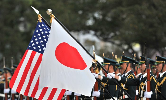 A unit of the Japanese Ground Self Defense Force honor guard holds national flags for a visiting U.S. Army general at the Defence Ministry in Tokyo on Oct. 28, 2011. (KAZUHIRO NOGI/AFP/Getty Images)
