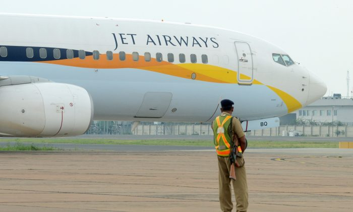 An Indian security official looks on as an aircraft of Jet Airways taxies at Indira Gandhi International Airport in New Delhi on Sept. 12, 2012. (Raveendran/AFP/GettyImages)