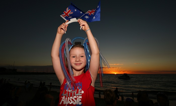 "A young girl proudly displays Australian flags as the sun sets at Bathers Beach on Jan. 26, 2017 in Fremantle, Australia. Fremantle Council held an alternative celebration on Jan. 28, following growing ""political correctness."" Local Fremantle businesses raised the money to hold the traditional Australia Day fireworks on the 26th despite the Council's decision. Australia Day, formerly known as Foundation Day, is the official national day of Australia and is celebrated annually on Jan. 26 to commemorate the arrival of the First Fleet to Sydney in 1788. (Paul Kane/Getty Images)"