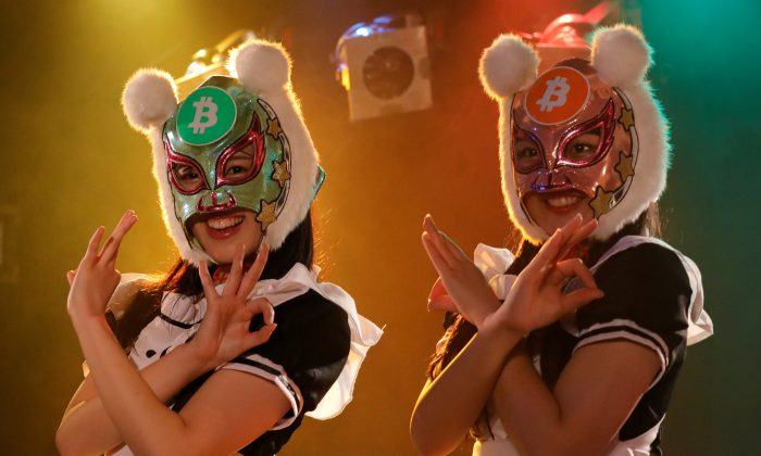 """Members of Japan's idol group """"Virtual Currency Girls"""" wearing cryptocurrency-themed masks pose after performing in their debut stage event in Tokyo, Japan, Jan. 12, 2018. (Reuters/Kim Kyung-Hoon)"""