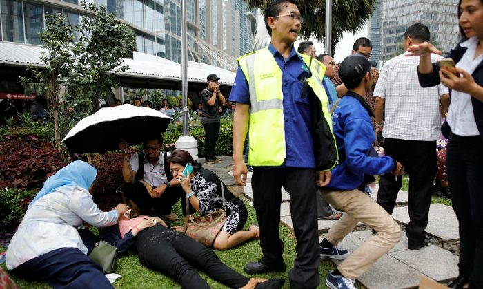 Injured people are treated outside the Indonesian Stock Exchange building following reports of a collapsed structure inside the building in Jakarta, Indonesia Jan. 15, 2018. (Reuters/Darren Whiteside)
