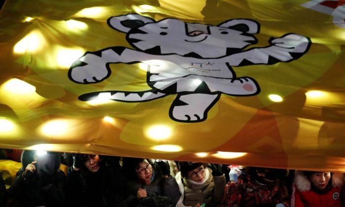 Women watch the Olympic torch relay under a giant banner depicting the 2018 PyeongChang Winter Olympics mascot Soohorang, in Seoul, South Korea, Jan. 13, 2018. (Reuters/Kim Hong-Ji)