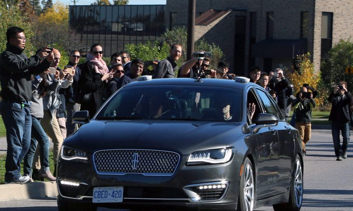 People watch as an autonomous car drives down an Ottawa street as the City of Ottawa andBlackberryQNXdemonstrate the vehicle on Oct. 12, 2017. (The Canadian Press/Fred Chartrand)