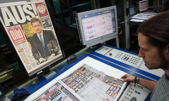 A printing technician matches a print of an issue in this file photo (Adam Berry/Getty Images)