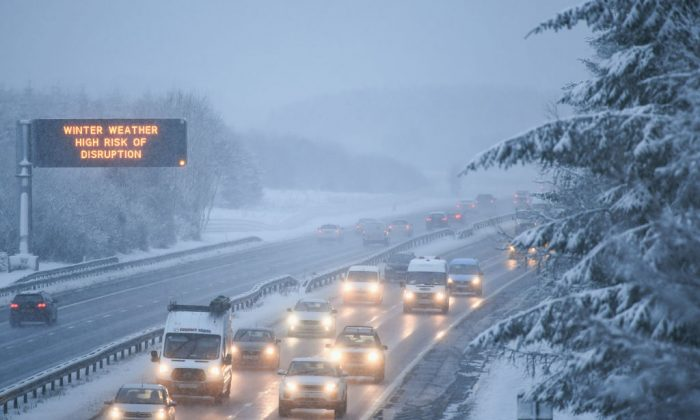 Motorists travel through a heavy snow shower on the M8 on Jan. 16, 2018 in Harthill, Scotland. Snow and sleet conditions are affecting large parts of Scotland with long delays affecting motorists on many roads including the M8 and M74. (Jeff J Mitchell/Getty Images)