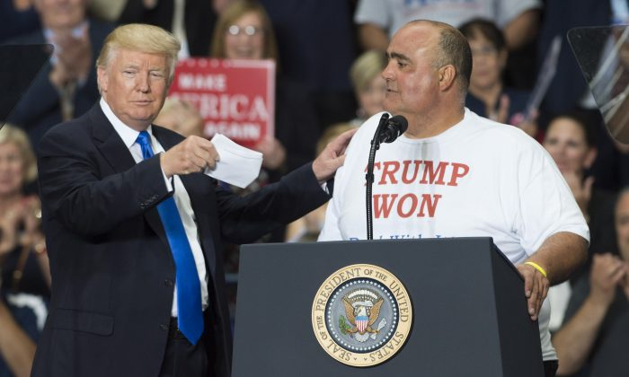Supporter Geno DiFabio (R) speaks alongside US President Donald Trump during a Make America Great Again rally at the Covelli Centre in Youngstown, Ohio, July 25, 2017. (SAUL LOEB/AFP/Getty Images)