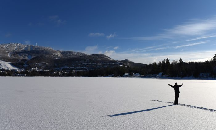 A man poses for a photo on frozen Lake Tremblant  in the Laurentides region of Quebec, Canada, at the foot of the Mont Tremblant on Dec. 24, 2017.  (Timothy A. Clary/AFP/Getty Images)