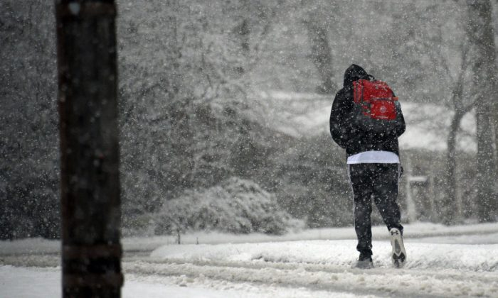 A man walks along Ridge Road as snow falls in Raleigh, North Carolina on January 17, 2018. (Lance King/Getty Images)