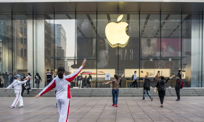 Elderly people perform square dance in front of an Apple store in Shanghai on Nov. 3, 2017. Apple is relinquishing control over its iCloud servers for Chinese users to a Chinese state-owned company in China, citing compliance with Chinese laws. (VCG via Getty Images)