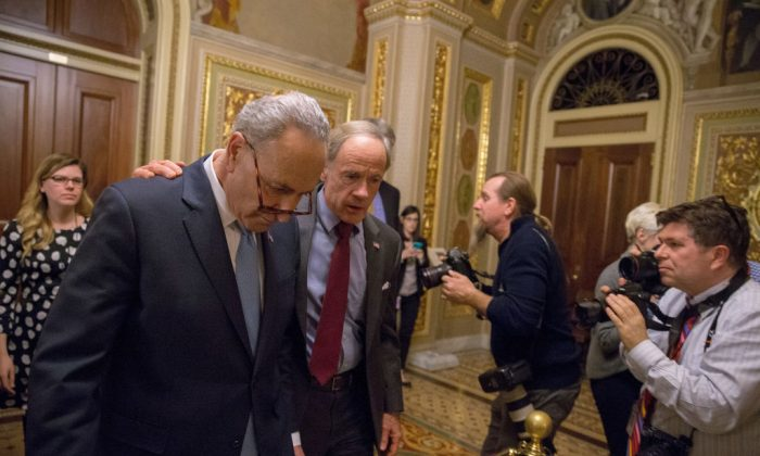 Senate Minority Leader Chuck Schumer (D-NY) and Senator Tom Carper (D-DE) walk out of a Democratic caucus meeting at the U.S. Capitol in Washington on Jan. 19, 2018. A continuing resolution to fund the government has passed the House of Representatives but failed in the Senate.  (Tasos Katopodis/Getty Images)