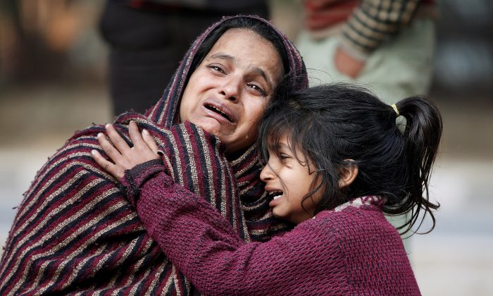 Relatives of a victim, who was killed in Saturday's fire in a warehouse, mourn as they wait outside a hospital in New Delhi, India, January 21, 2018. (Reuters/Adnan Abidi)