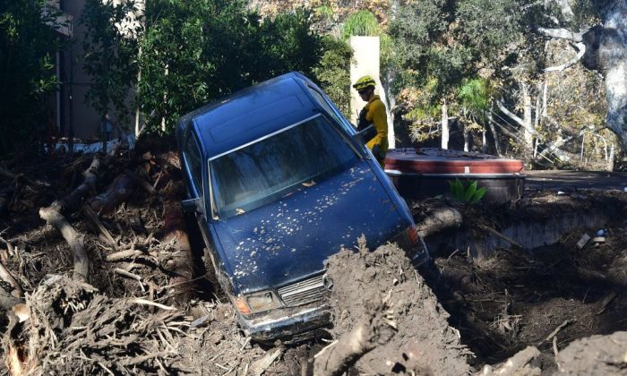 A firefighter stands near a car caught up in a mud slide in Montecito, California Jan. 12, 2018. (Frederic J. Brown/AFP/Getty Images)