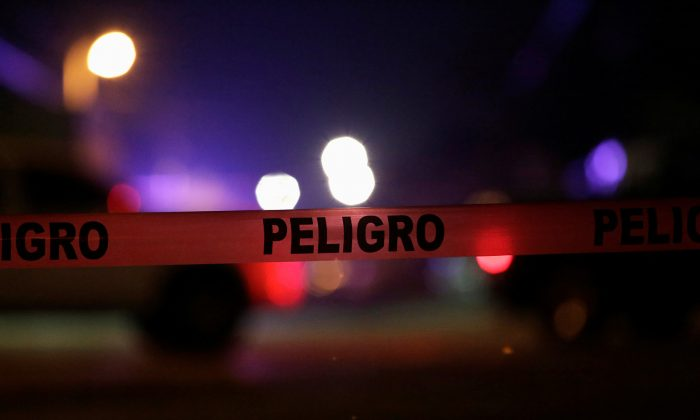 """In this file image, a police cordon reading """"Danger"""" is pictured at a crime scene where unknown assailants gunned down people at a garage in Ciudad Juarez, Mexico, Jan. 4, 2018. (Reuters/Jose Luis Gonzalez)"""