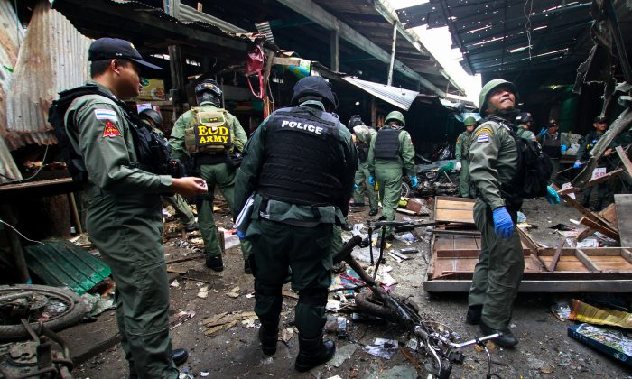 Military personnel and police officers inspect the site of a bomb attack at a market in the southern province of Yala, Thailand, Jan. 22, 2018. (Reuters/Surapan Boonthanom)
