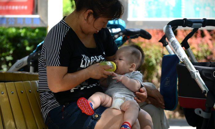 A woman feeds a baby with a bottle in a residential area in Beijing on August 8, 2013. (Wang Zhao/AFP/Getty Images)