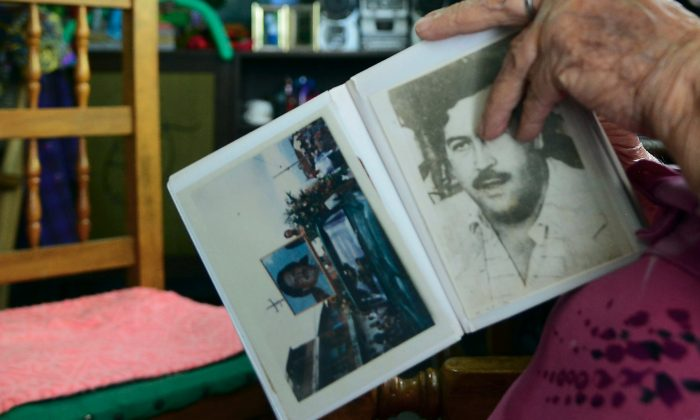 A woman shows an album with pictures of late Colombian drug lord Pablo Escobar at her home in the Pablo Escobar neighborhood in Medellin, Colombia, on Dec. 2, 2015. Escobar is still revered by many people. (Raul Arboleda/AFP/Getty Images)