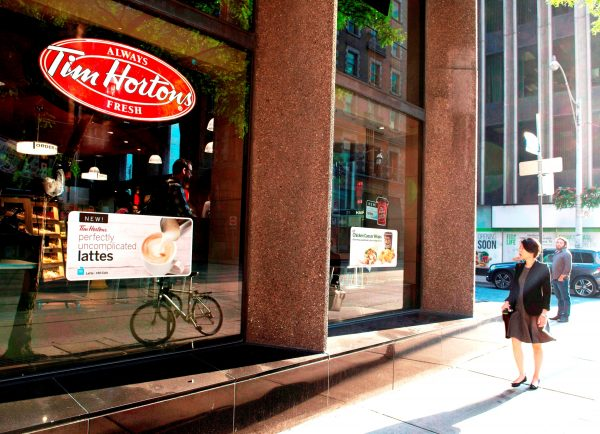 A woman walks past aTimHortonscoffee shop in Toronto. (The Canadian Press/Doug Ives)