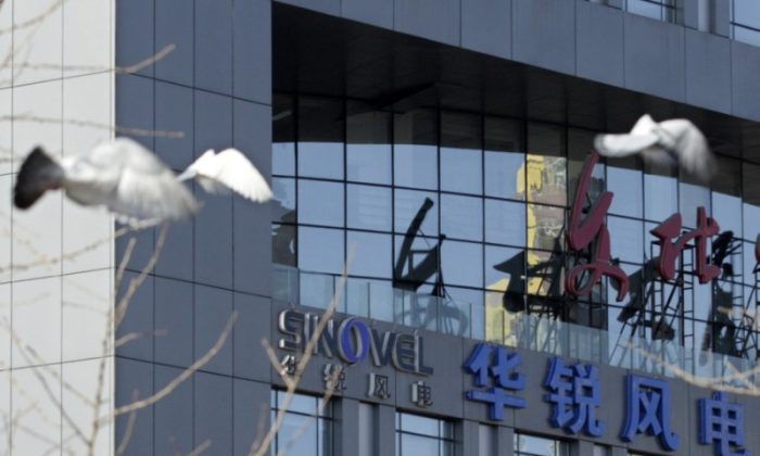 Pigeons fly past the company logo of Sinovel Wind Co., Ltd. outside its head office in Beijing, on Jan. 6, 2011. (Soo Hoo Zheyang/REUTERS)