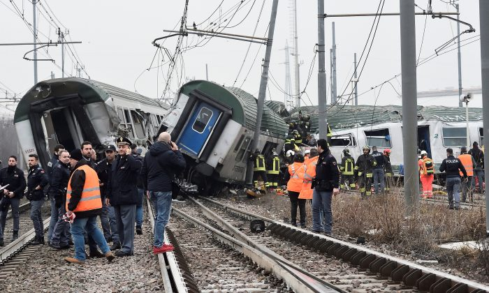 Rescue workers and police officers stand near derailed trains in Pioltello, on the outskirts of Milan, Italy, Jan. 25, 2018. (Reuters/Stringer)