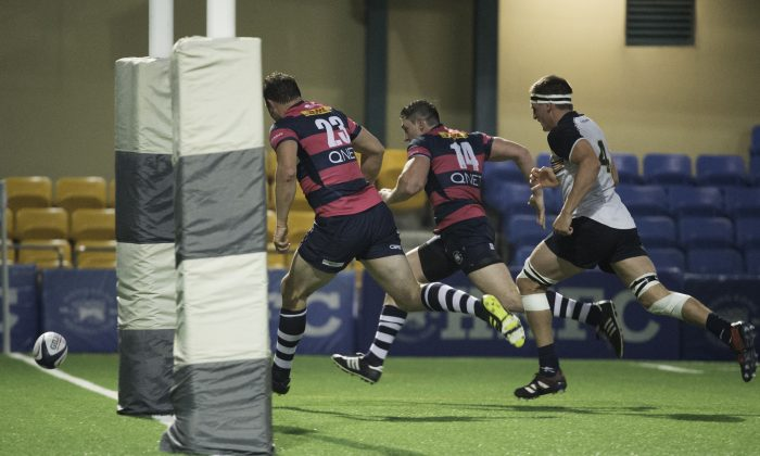 Natixis HKFC players Marno Meyer (23) and Charles Higson Smith race to score ahead of Herbert Smith Freehills HKCC  player Lawrence Babe in the HKRU Premiership at HKFC on Saturday Jan 20. (Bill Cox/Epoch Times)