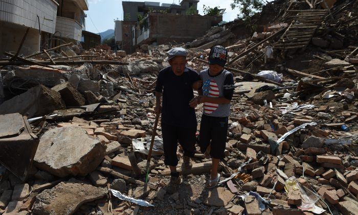 An elderly earthquake survivor is helped by his grandson as they walk through the rubble of collapsed houses at Longtoushan, in Ludian County, Yunnan Province in southwestern China, on Aug. 7, 2014. (Greg Baker/AFP/Getty Images)