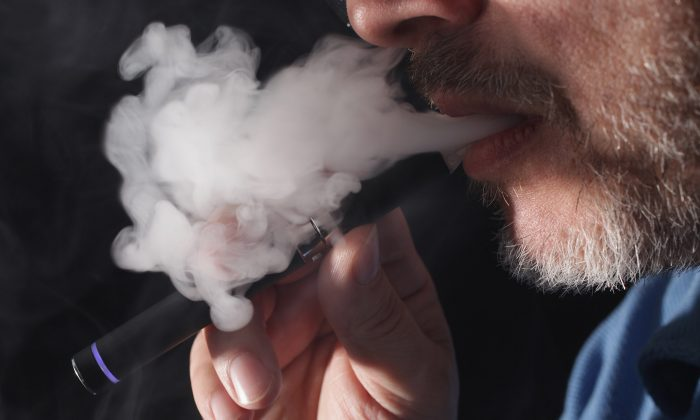In this photo illustration the owner of a shop that sells electronic cigarettes demonstrates how to use one in Berlin, Germany on March 1, 2012. (Sean Gallup/Getty Images)