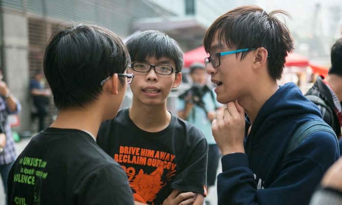 Joshua Wong (C), one of three Nobel Peace Prize nominees who led the 2014 pro-democracy protests in Hong Kong, chats with student leaders during the protests, on Nov. 18, 2014. (Benjamin Chasteen/The Epoch Times)