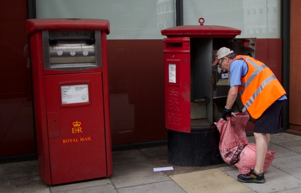 A postman empties a Royal Mail post box in London on July 10, 2013. (Andrew Cowie/AFP/Getty Images)