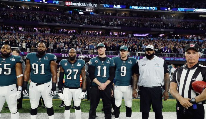 Brandon Graham #55, Fletcher Cox #91, Malcolm Jenkins #27, Carson Wentz #11 and Nick Foles #9 of the Philadelphia Eagles stand for the national anthem prior to Super Bowl LII against the New England Patriots at U.S. Bank Stadium on Feb. 4, 2018 in Minneapolis, Minnesota.  (Photo by Elsa/Getty Images)