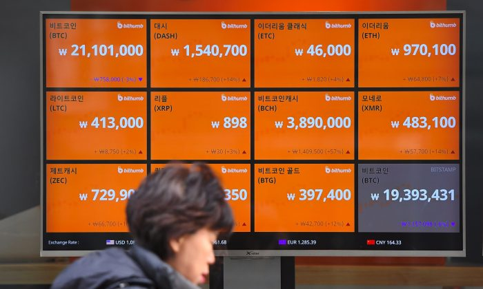 A woman walks past a screen showing exchange rates of cryptocurrencies at an exchange in Seoul on Dec. 20, 2017. A South Korean cryptocurrency exchange shut down on Dec. 19, after losing 17 percent of its assets in a hacking – its second cyberattack this year, with North Korea accused of being behind the first. (JUNG YEON-JE/AFP/Getty Images)
