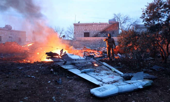 A fighter taking a picture of a downed Sukhoi-25 fighter jet in Syria's northwest province of Idlib on Feb. 3, 2018. (Omar Haj Kadour/AFP/Getty Images)