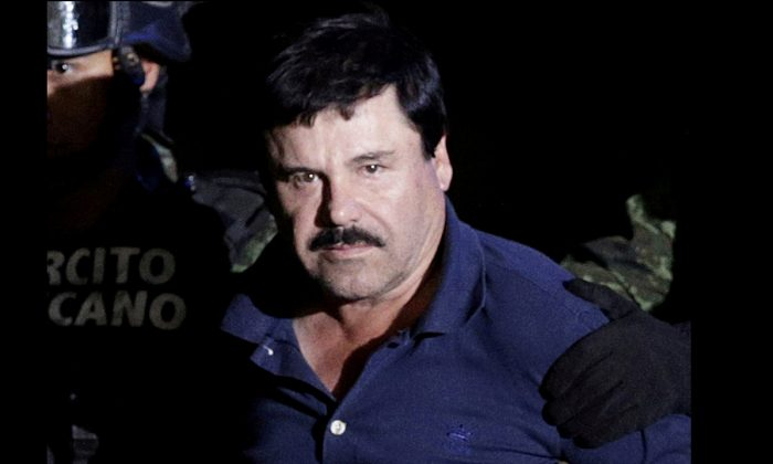 "Recaptured drug lord Joaquin ""El Chapo"" Guzman is escorted by soldiers at the hangar belonging to the office of the Attorney General in Mexico City, Mexico, on Jan 8, 2016. (Henry Romero/Reuters)"