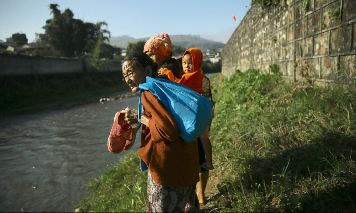 Refugees from Burma stand beside a river near the China-Burma border in Wanding, in China's southwest Yunnan province on Nov. 30, 2016. Thousands of refugees have fled into China in November due to fighting in northern Burma, and are being housed in temporary shelters along the border. Locals near the Chinese border in Burma's northern state of Shan said they were fleeing heavy fighting between the army and four armed ethnic groups, including the powerful Kachin Independence Army. (STR/AFP/Getty Images)