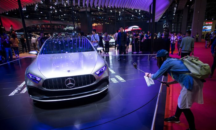 Visitors look at a sedan car from German carmaker Mercedes during the 17th Shanghai International Automobile Industry Exhibition in Shanghai on April 24, 2017. (Johannes Eisele/AFP/Getty Images)