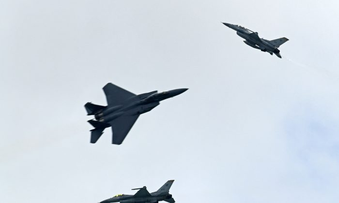 A Singapore Air Force aerobatic team comprising of two F-16Cs and an F-15SG fighter aircraft performs an aerial display during a media preview for the Singapore Airshow in Singapore on February 4, 2018. (Roslan Rahman/AFP/Getty Images)